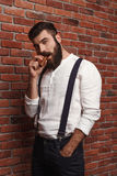 Brutal young handsome man smoking cigar over brick background. Royalty Free Stock Photo