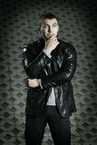 Brutal young man in a leather jacket Stock Images