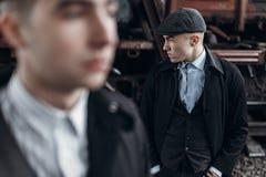 Brutala gangster som poserar på bakgrund av den järnväg vagnen engla Arkivfoto