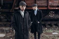 Brutala gangster som poserar på bakgrund av den järnväg vagnen engla Royaltyfri Fotografi