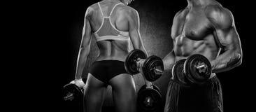 Brutale atletische vrouw die omhoog spieren met domoren pompen royalty-vrije stock fotografie