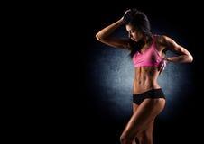Brutale atletische vrouw die omhoog spieren met domoren pompen royalty-vrije stock afbeelding