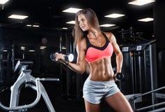 Brutale atletische vrouw die omhoog spieren met domoren pompen royalty-vrije stock afbeeldingen