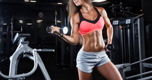 Brutale atletische vrouw die omhoog spieren met domoren pompen royalty-vrije stock foto's