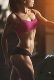 Brutale atletische vrouw die omhoog spieren pompen met stock foto