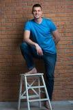 Brutale blootvoetse mens in stoel het stellen tegen een bakstenen muur Stock Foto's