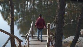 Brutale gebaarde mensengang aan een meer door brug witn een bijl in zijn hand Jonge gebaarde kerel met een bijl in openlucht stock video