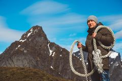 Brutale mens met een kabel op zijn schouder tegen de achtergrond van de bergen en de blauwe hemel De ruimte van het exemplaar Kan stock foto