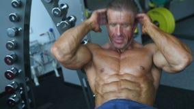 Brutale sterke bodybuilder atletische mensen die omhoog spieren met domoren pompen stock footage