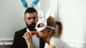 Brutalna para w rzemiennej maskowej objadanie marchewce lubi króliki Backgrounde Odizolowywaj?cy w bielu zabawna para nami?tny zdjęcie wideo