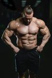 Brutalnego silnego bodybuilder sportowi mężczyzna pompuje up mięśnie z d Fotografia Stock