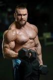 Brutalnego silnego bodybuilder sportowi mężczyzna pompuje up mięśnie z d Obraz Royalty Free