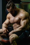 Brutalnego silnego bodybuilder sportowi mężczyzna pompuje up mięśnie z d Fotografia Royalty Free