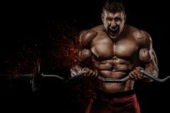 Brutalnego silnego mięśniowego bodybuilder sportowy mężczyzna pompuje w górę mięśni z barbell na czarnym tle trening obrazy royalty free