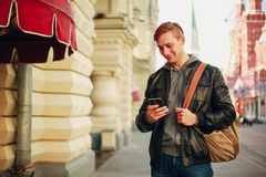 Brutalni mężczyzn stojaki w mieście i używają smartphone ono uśmiecha się zdjęcie stock
