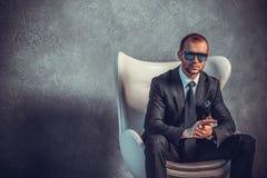 Brutalni seksowni biznesmeni siedzi na krześle w kostiumu z krawatem i okularami przeciwsłonecznymi Obrazy Royalty Free