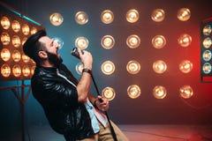 Brutalny brodaty piosenkarz z mikrofonem na scenie zdjęcie royalty free