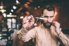 Brutalny i poważny hairfresser trzyma nożyce w jego prawej ręce i patrzeje przez on kamera Także jest mężczyzna obrazy stock