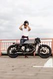 Brutalny mężczyzna blisko jego cukiernianego setkarza zwyczaju motocyklu Fotografia Stock
