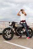 Brutalny mężczyzna blisko jego cukiernianego setkarza zwyczaju motocyklu Obraz Stock