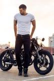 Brutalny mężczyzna blisko jego cukiernianego setkarza zwyczaju motocyklu obraz royalty free