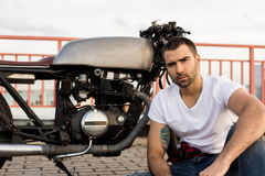Brutalny mężczyzna blisko jego cukiernianego setkarza zwyczaju motocyklu Fotografia Royalty Free