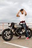 Brutalny mężczyzna blisko jego cukiernianego setkarza zwyczaju motocyklu Zdjęcie Stock