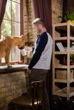 Brutalny mężczyzna pije coffe okno, jego pies patrzeje w jego kubek Zdjęcia Stock