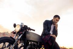 Brutalny mężczyzna siedzi na cukiernianym setkarza zwyczaju motocyklu Zdjęcia Stock