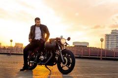 Brutalny mężczyzna siedzi na cukiernianym setkarza zwyczaju motocyklu Zdjęcie Stock