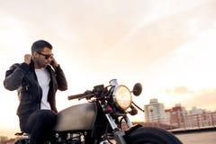 Brutalny mężczyzna siedzi na cukiernianym setkarza zwyczaju motocyklu Obrazy Stock