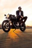 Brutalny mężczyzna siedzi na cukiernianym setkarza zwyczaju motocyklu Obraz Royalty Free