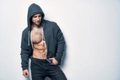 Brutalny nagi mięśniowy mężczyzna ubierał w popielatym hoodie zdjęcie stock