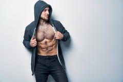 Brutalny nagi mięśniowy mężczyzna ubierał w popielatym hoodie obraz royalty free