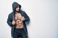 Brutalny nagi mięśniowy mężczyzna ubierał w popielatym hoodie fotografia royalty free