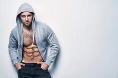 Brutalny nagi mięśniowy mężczyzna ubierał w popielatym hoodie zdjęcie royalty free