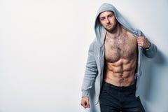 Brutalny nagi mięśniowy mężczyzna ubierał w popielatym hoodie obrazy royalty free
