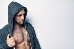 Brutalny nagi mięśniowy mężczyzna ubierał w popielatym hoodie zdjęcia royalty free