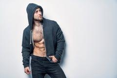 Brutalny nagi mięśniowy mężczyzna ubierał w popielatym hoodie fotografia stock