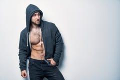 Brutalny nagi mięśniowy mężczyzna ubierał w popielatym hoodie zdjęcia stock