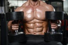 Brutalny silny bodybuilder mężczyzna pompuje up mięśnie i taborowego gym zdjęcie royalty free