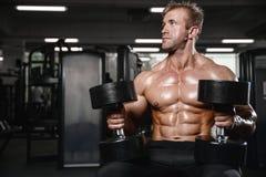 Brutalny silny bodybuilder mężczyzna pompuje up mięśnie i taborowego gym Zdjęcia Royalty Free