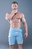 Brutalny silny bodybuilder mężczyzna pozuje w studiu na popielatym backgroun Obrazy Royalty Free