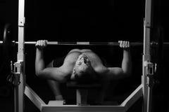 Brutalny sportowy mężczyzna pompuje up mięśnie Fotografia Stock