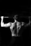 Brutalny sportowy mężczyzna pompuje up mięśnie Zdjęcia Stock