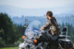 Brutalt cyklistsammanträde på hans motorcykel på en solig dag royaltyfri foto