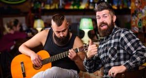 Brutalt för Hipster som uppsökas med vännen i bar Manlekgitarr i bar r avkoppling arkivfoton