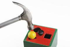 Brute force. Forcing a ball into a triangular hole with the help of a hammer stock image