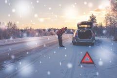 Bruten bil på en snöig vinterväg fotografering för bildbyråer