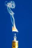 Bruten brännskada för ljus kula ut med flamman på blått Arkivfoto
